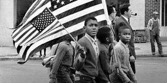 MONTGOMERY, AL - MARCH 25: Selma to Montgomery civil rights marchers, with Negro boys holding large and small American flags. Man seated on windowsill in building in background - On March 25, 1965 in Montgomery, Alabama. (Photo by Stephen F. Somerstein)